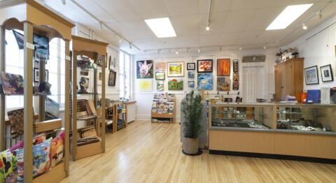 Image de la boutique au CCMF, vue de face du comptoir et des œuvres au murs